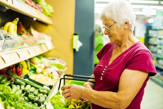 Older woman selecting vegetables in a grocery store.
