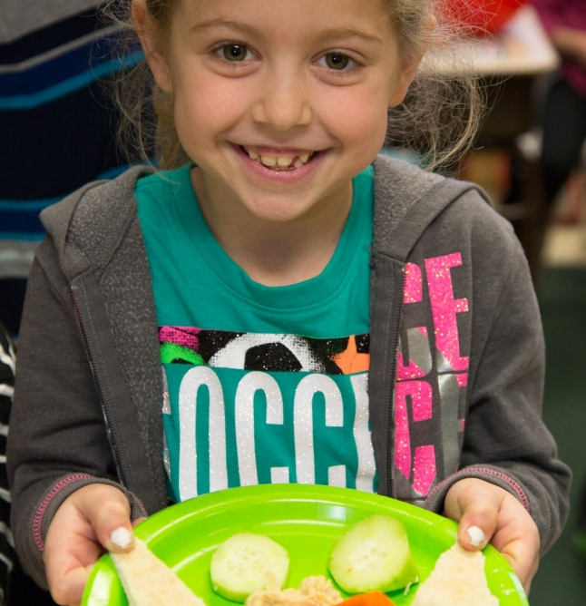 young girl holding a plate of healthy snacks