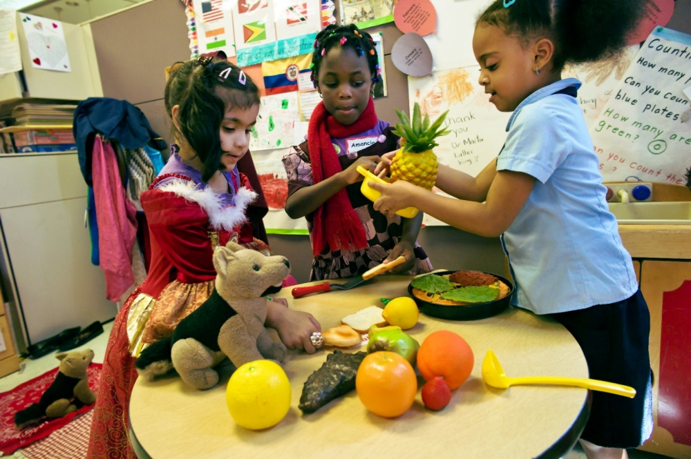 Students playing with toy fruit in their classroom