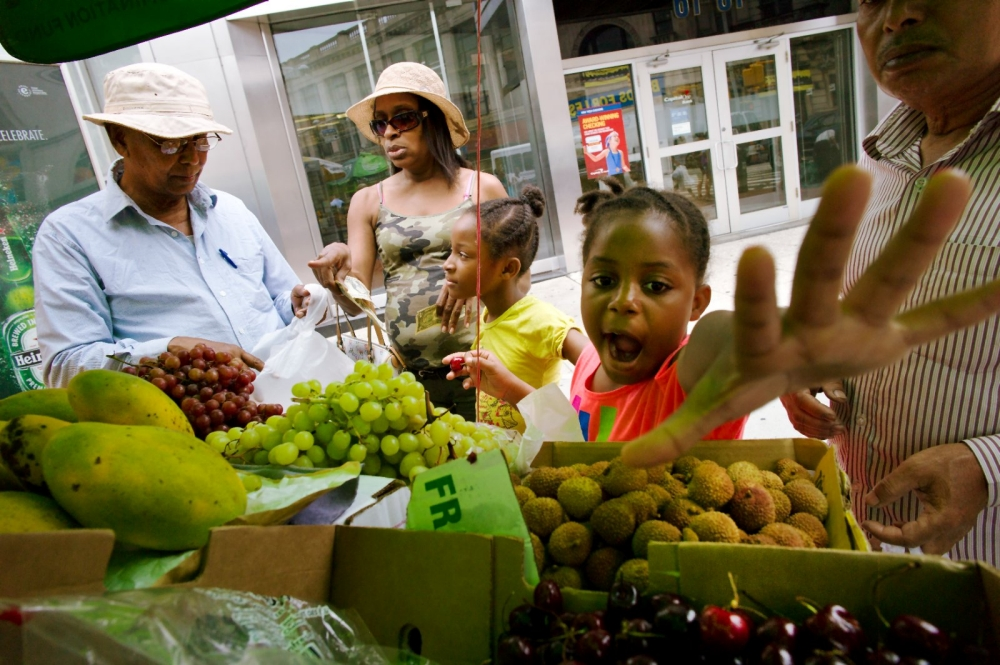 Children and their families reaching for fruit at an outdoor stand