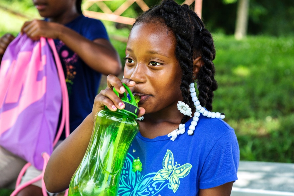 Young girl smiling while drinking from her water bottle