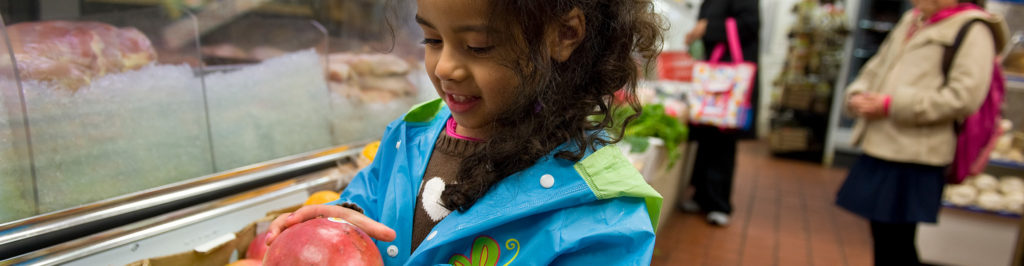 Young girl smiling while holding a piece of fruit