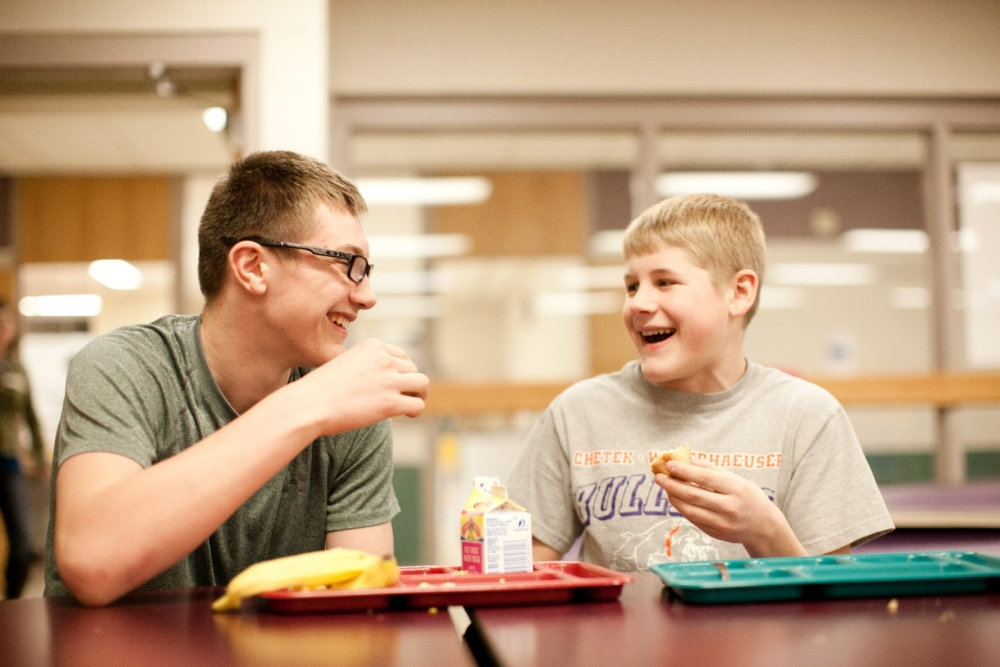 Two young boys enjoy their lunch
