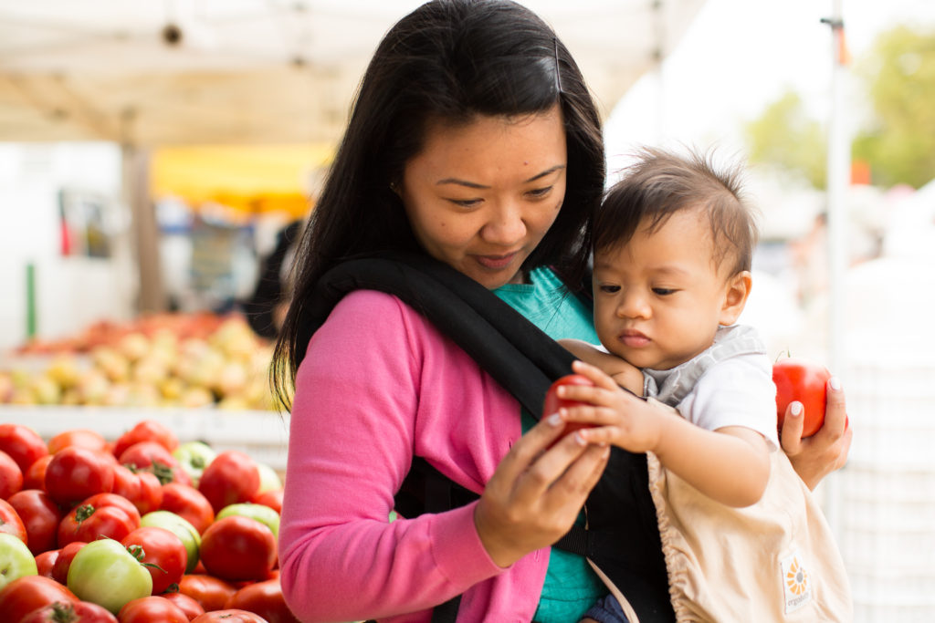 Mother and child holding a tomato at the grocery store
