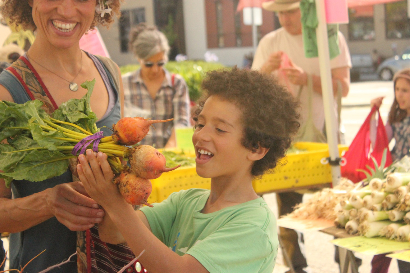 Boy looking at vegetables at farmers market