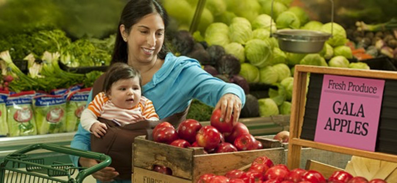Woman with child buying apples from market.