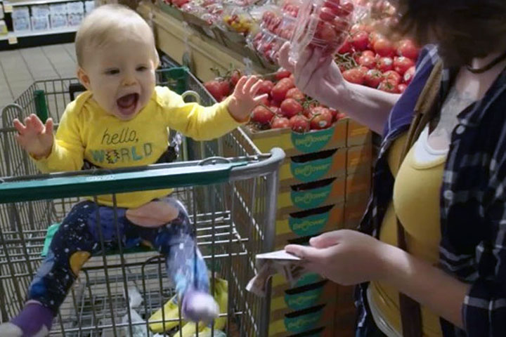 woman buys groceries with baby