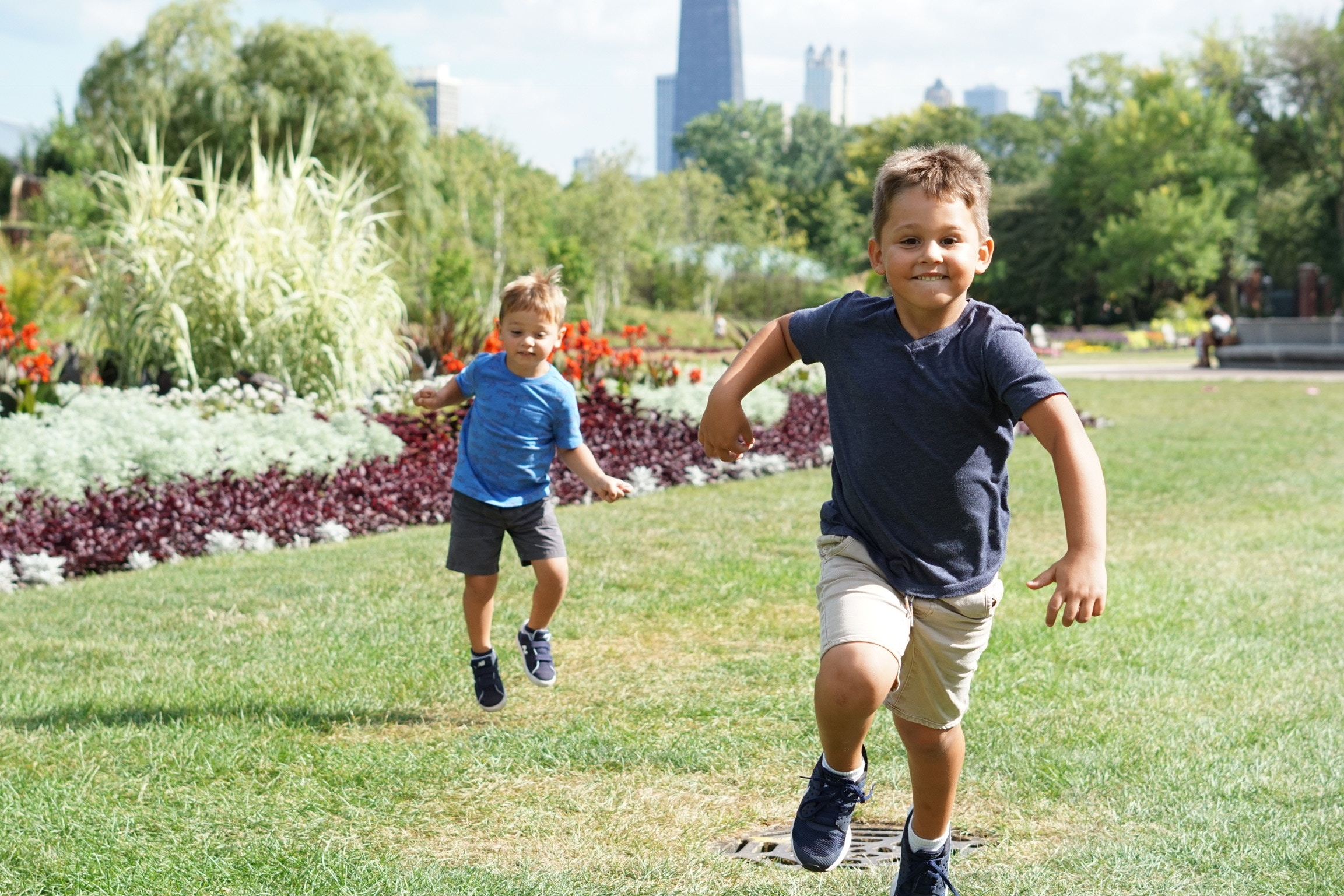Two young boys running outside.
