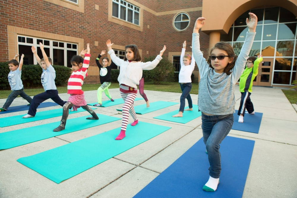 Kids doing yoga outside their school.