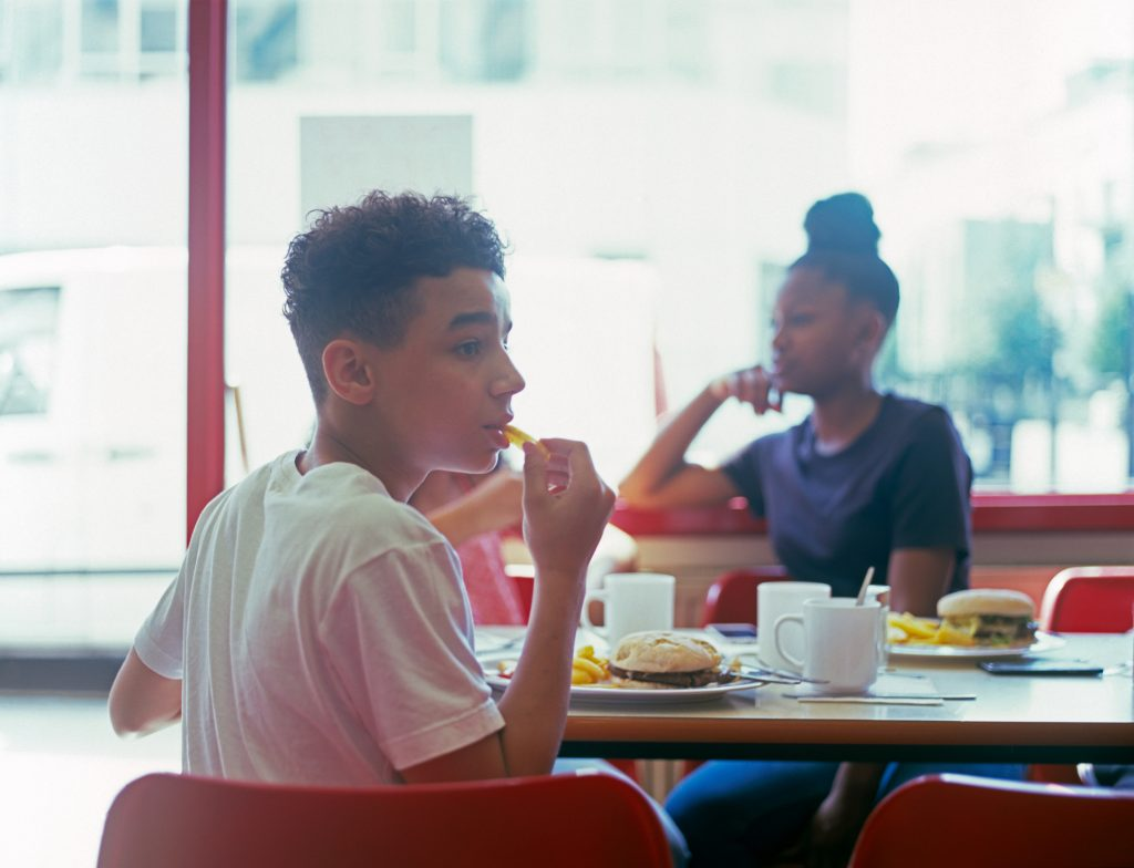 Teenage boy in cafe eating burger and fries