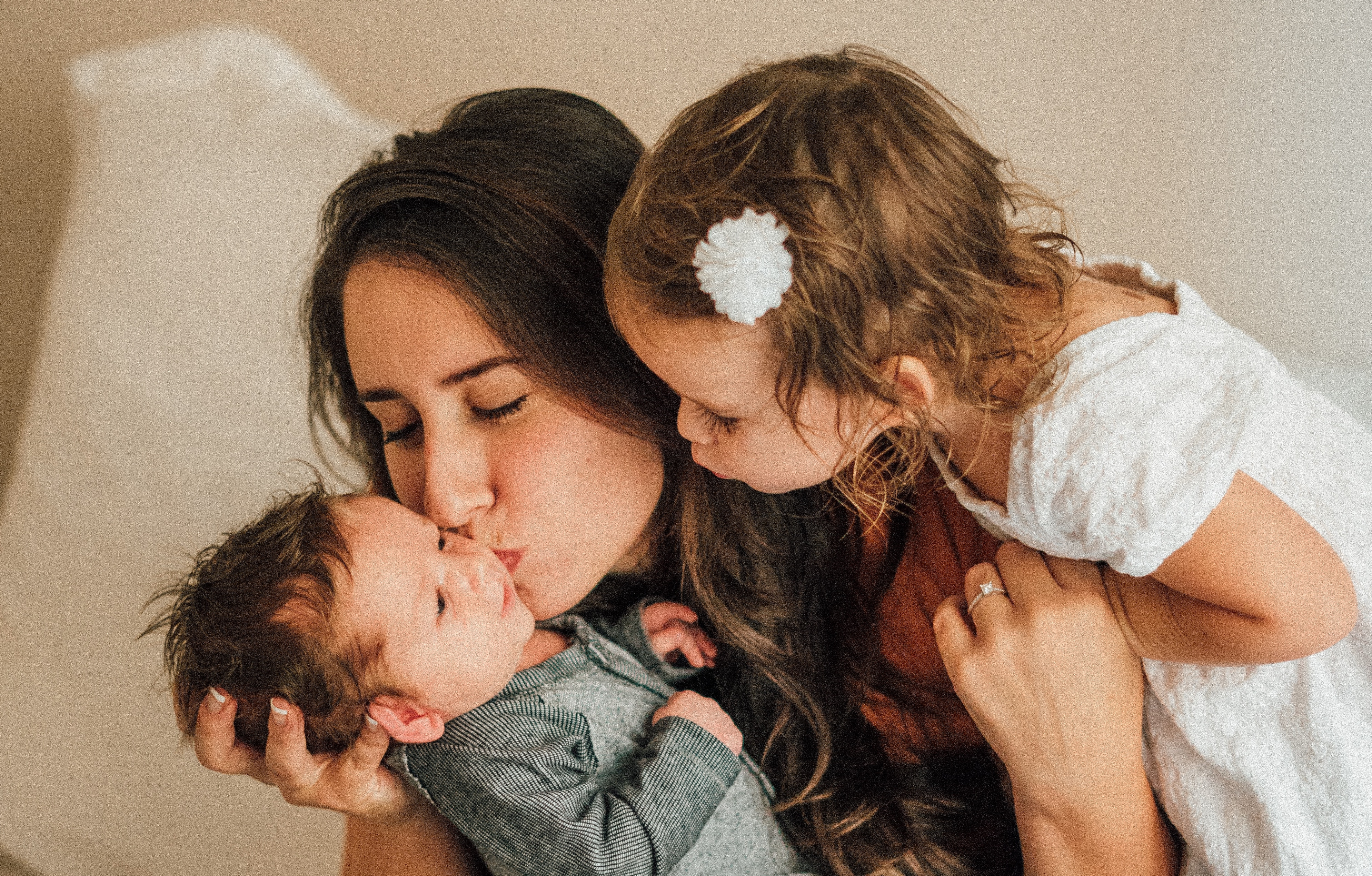 Woman kissing baby with daughter on other side.