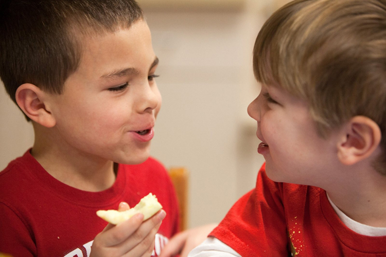 Two young boys enjoy a healthy snack at First United Methodist Preschool in Murfreesboro, Tennessee.