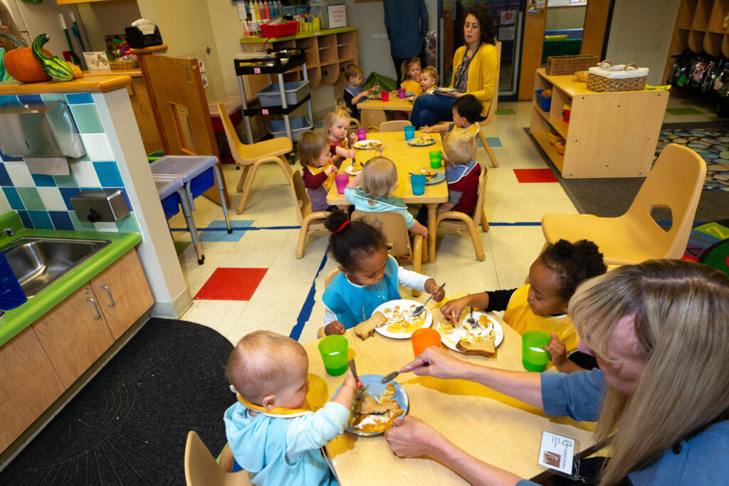 Young children eating meal at early childcare center.