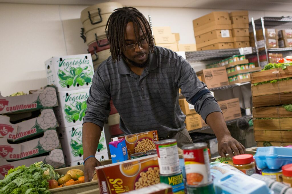 Image of man selecting food in food bank.