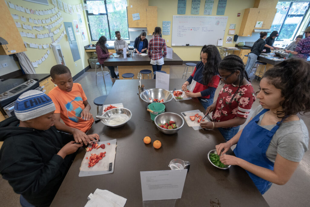 Young people slicing fruits and vegetables