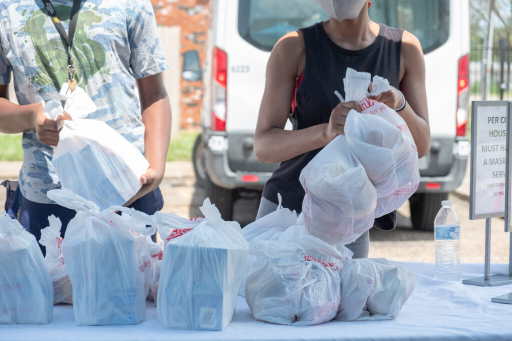 Families pick up school meals at a food distribution site.