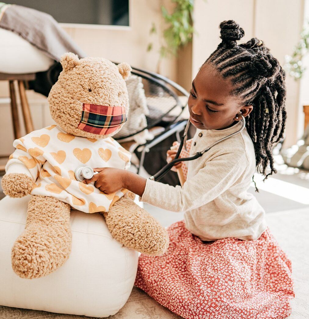 Little girl playing doctors with teddy bear
