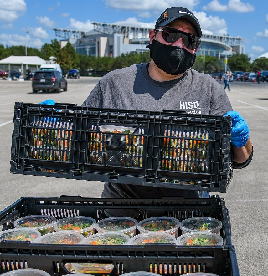 Man carries crate of food at COVID distribution site