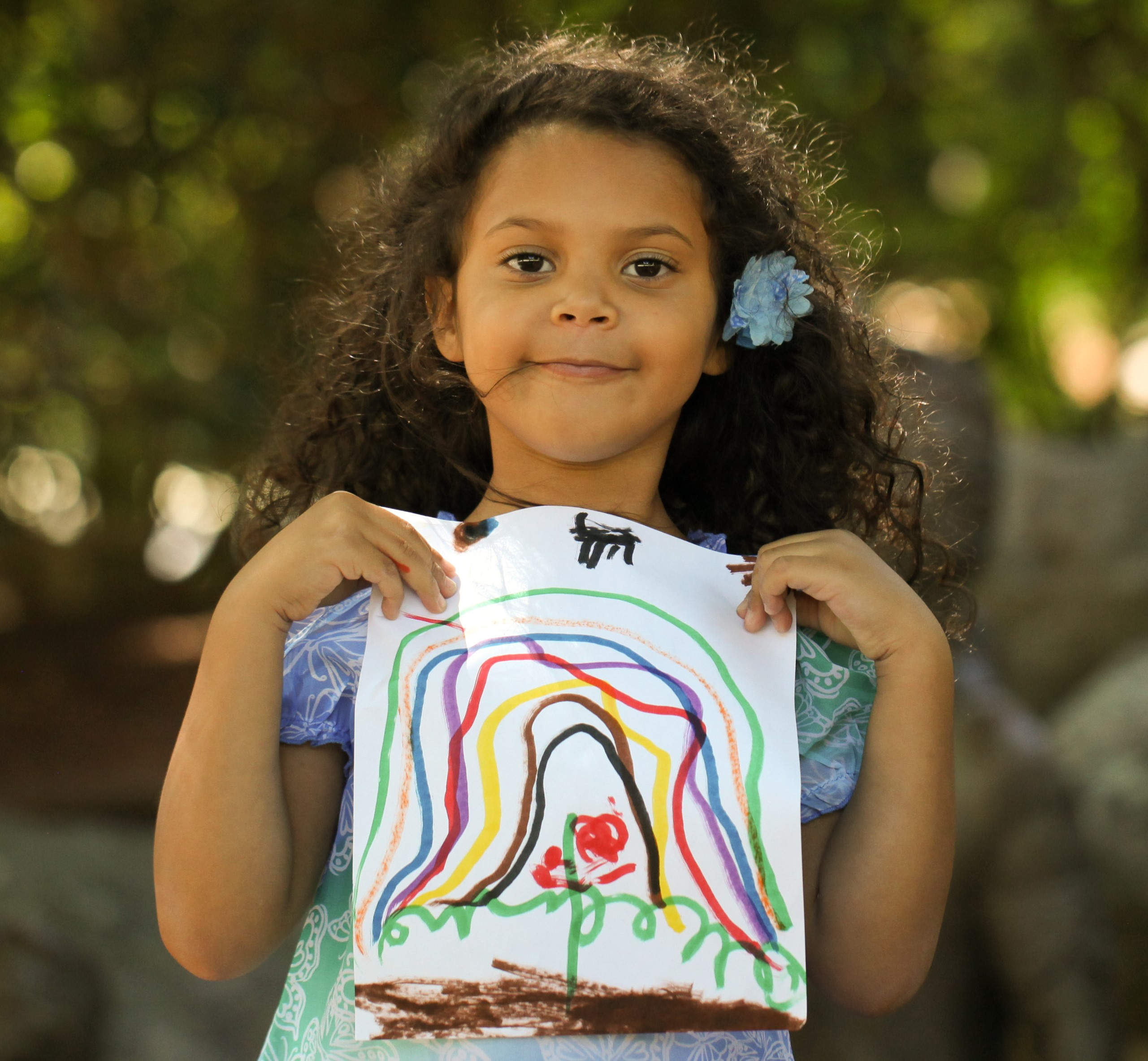 Young girl holds drawing of rainbow