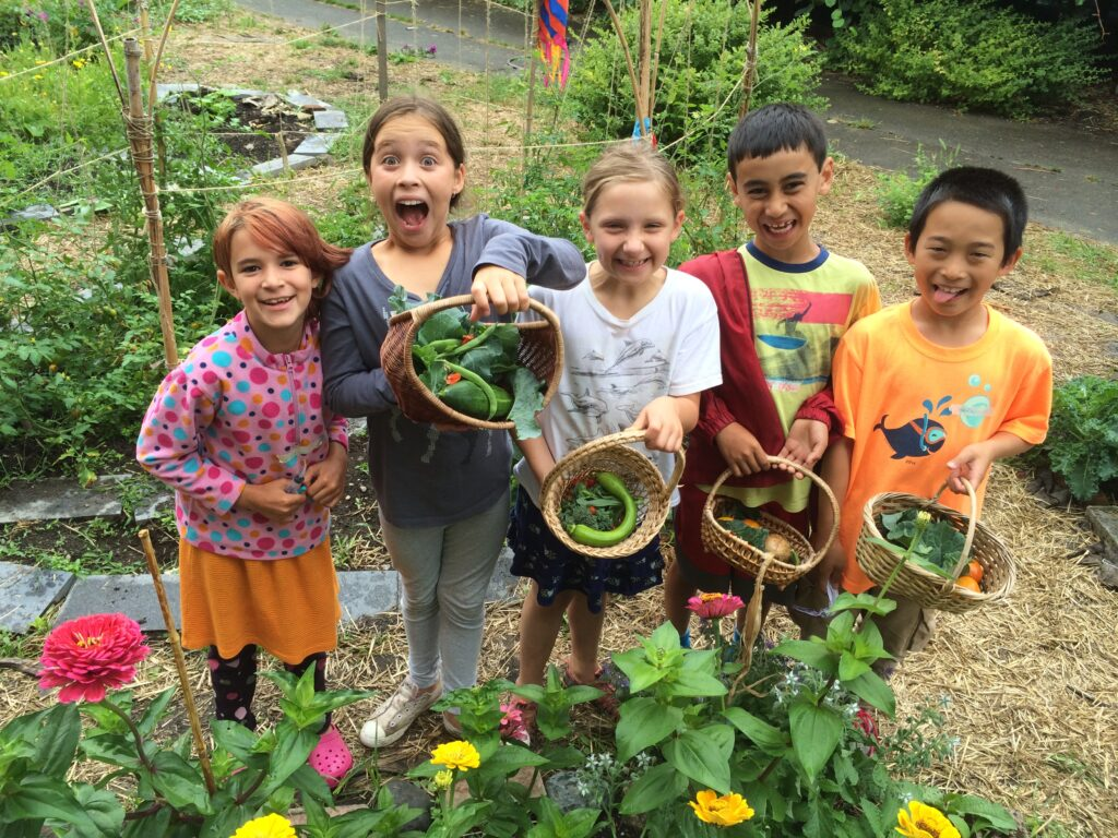 A group of kids hold vegetables