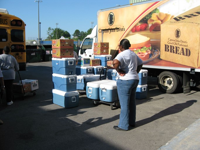 A woman unloads food from a bus