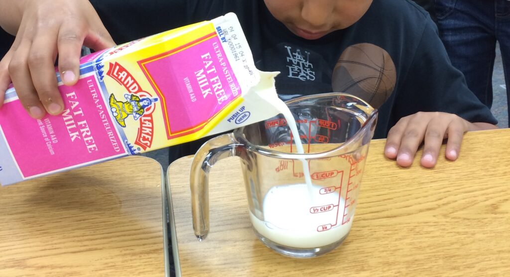 Student pouring milk into measuring cup