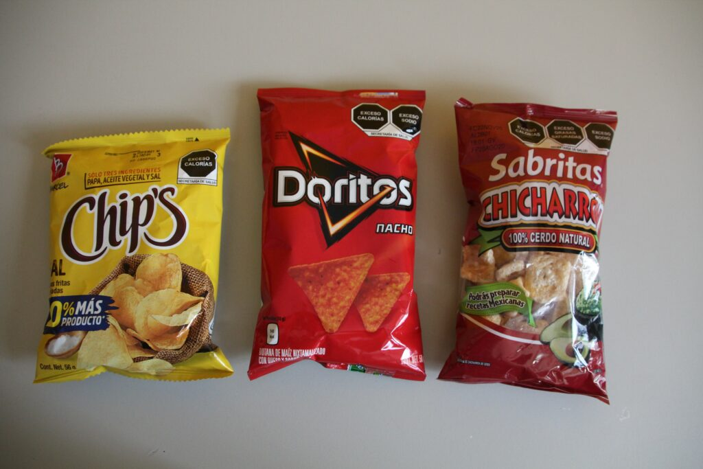 A photo showing health warning labels on bags of chips and snacks