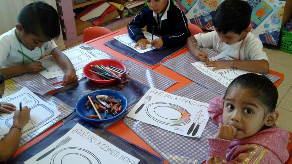 Children coloring pictures to show what they will eat
